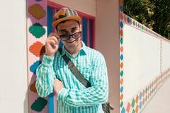 Giovane modello bello felice sicuro alla moda dell'uomo in t-breve blu con ed occhiali da sole del cappuccio Priorità bassa del r Fotografia Stock