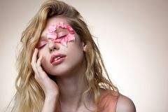Giovane modello che posa per la rivista moderna con i petali sul fronte fotografia stock