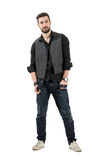 Giovane modello di moda maschio che tiene le sue bretelle che esaminano macchina fotografica Fotografia Stock