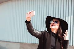 Giovane modello felice che prende selfie sullo smartphone La donna porta il cappello a Fotografia Stock Libera da Diritti