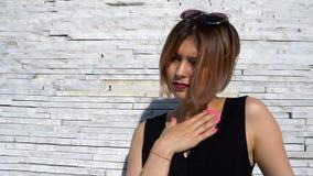 Giovane modello femminile alla moda alla moda in occhiali da sole in un possing nero del vestito all'aperto video d archivio