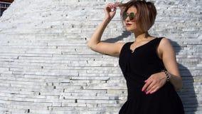 Giovane modello femminile alla moda alla moda in occhiali da sole in un possing nero del vestito all'aperto stock footage