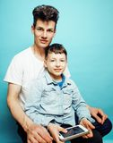 Giovane modello grazioso dell'uomo con il piccolo figlio sveglio che gioca insieme, concetto moderno della gente di stile di vita fotografia stock libera da diritti