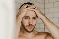 Giovane modello maschio attraente Washing Hair nella doccia bagnata delle mattonelle moderne d'avanguardia del sottopassaggio immagini stock libere da diritti