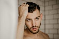 Giovane modello maschio attraente Washing Hair nella doccia bagnata delle mattonelle moderne d'avanguardia del sottopassaggio fotografia stock
