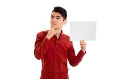 Giovane modello maschio premuroso alla moda che posa con il cartello in mani isolate su fondo bianco Immagine Stock Libera da Diritti