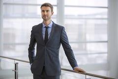 Giovane moderno esecutivo sicuro dalla finestra all'alto ufficio moderno di aumento Immagini Stock Libere da Diritti