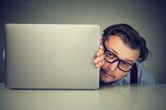 Giovane modesto che si nasconde dietro il computer portatile immagini stock libere da diritti