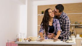 Giovane moglie che dà affetto al suo marito mentre cucinando immagini stock