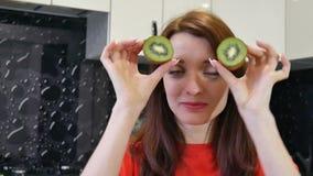 Giovane moglie sveglia che gioca con due metà del kiwi mentre prepearing alimento alla cucina Concetto umano positivo di emozioni stock footage