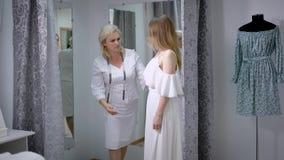 Giovane montaggio della sposa sul vestito da sposa nell'adattamento dello studio Sarti femminili che cercano il suo modello e che video d archivio