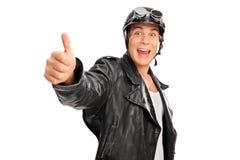 Giovane motociclista allegro che dà un pollice su Immagini Stock
