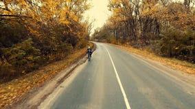 Giovane motociclista che cicla su una strada con una foresta scenica di autunno video d archivio