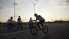 Giovane in motociclista esperto che pratica una tecnica acrobatica di rotazione 360 con il suo esterno degli amici al rallentator video d archivio