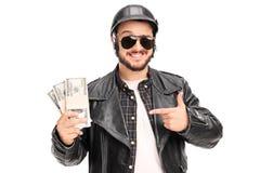 Giovane motociclista maschio che tiene poche pile di soldi Fotografia Stock