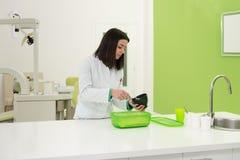 Giovane muffa femminile di Working On The del dentista fotografia stock