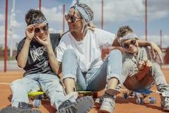 Giovane mummia che si siede con i suoi figli al campo da giuoco Concetto 'nucleo familiare' felice fotografia stock libera da diritti