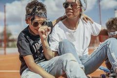 Giovane mummia che si siede con i suoi figli al campo da giuoco Concetto 'nucleo familiare' felice immagine stock