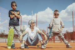 Giovane mummia che si siede con i suoi figli al campo da giuoco Concetto 'nucleo familiare' felice fotografia stock