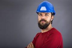 Giovane muratore sicuro con l'elmetto protettivo e armi piegate Fotografie Stock