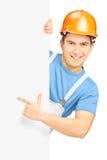 Giovane muratore sorridente con il casco che indica sul pannello Fotografia Stock Libera da Diritti