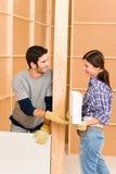 Giovane muro di mattoni della costruzione delle coppie di miglioramento domestico immagini stock libere da diritti