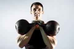 Giovane muscolare che fa esercizio pesante per il bicipite Fotografia Stock Libera da Diritti