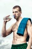 Giovane muscolare dopo una bottiglia bevente di allenamento di acqua Fotografie Stock Libere da Diritti