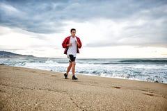 Giovane muscolare nel funzionamento luminoso degli abiti sportivi sulla spiaggia lungo il mare, effetto di HDR fotografie stock libere da diritti