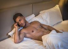 Giovane muscolare senza camicia a letto che parla sul telefono cellulare fotografie stock