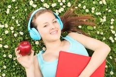 Giovane musica d'ascolto femminile e tenere una mela, sul gr verde Immagine Stock