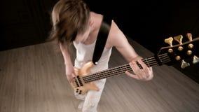 Giovane musicista maschio in vestiti bianchi con un basso elettrico beige su un fondo nero Musica espressiva del giocatore di bas archivi video