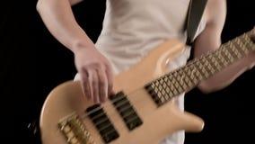 Giovane musicista maschio in vestiti bianchi con un basso elettrico beige su un fondo nero Musica espressiva del giocatore di bas stock footage