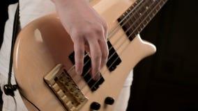 Giovane musicista maschio in vestiti bianchi con un basso elettrico beige su un fondo nero Musica espressiva del giocatore di bas video d archivio