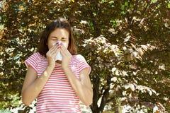 Giovane naso di salto grazioso della ragazza davanti all'albero Concetto di allergia della primavera Fotografia Stock