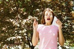 Giovane naso di salto grazioso della ragazza davanti all'albero Concetto di allergia della primavera Fotografie Stock Libere da Diritti