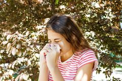 Giovane naso di salto grazioso della ragazza davanti all'albero Concetto di allergia della primavera Immagine Stock