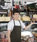 Giovane negozio di Gesturing Towards Cheese del rappresentante Immagini Stock Libere da Diritti