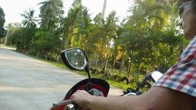 Giovane nel viaggiatore degli occhiali da sole che conduce motocicletta sulla strada soleggiata tropicale Movimento lento Fine in stock footage