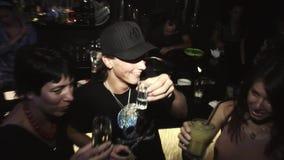 Giovane nella bevanda del berretto nero con le ragazze alla barra sul partito in night-club celebrazione intrattenimento stock footage