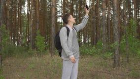 Giovane nella foresta che prova a prendere un segnale mobile stock footage