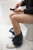Giovane nella toilette facendo uso dello Smart Phone Fotografia Stock Libera da Diritti