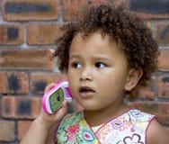 Giovane neonata nera su un telefono delle cellule del giocattolo Fotografia Stock Libera da Diritti