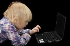 Giovane neonata sul suo computer portatile Immagini Stock