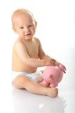 Giovane neonato che gioca con la banca piggy dentellare Fotografie Stock Libere da Diritti