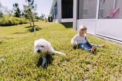 Giovane neonato sveglio ed adorabile del bambino che gioca nell'erba di verde del cortile e che sorride alla macchina fotografica immagine stock