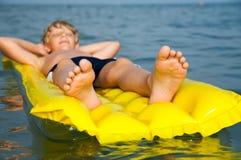 Giovane nuoto del ragazzo sul materasso nel mare fotografie stock