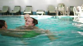 Giovane nuoto della famiglia nello stagno insieme al suo piccolo bambino sveglio Il ragazzo sta nuotando sul retro di sua madre archivi video