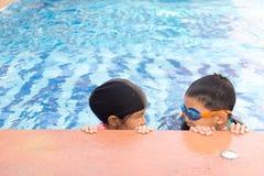Giovane nuoto della ragazza e del ragazzo nello stagno fotografia stock libera da diritti
