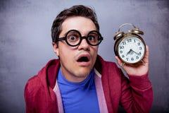 Giovane in occhiali con la sveglia del metallo Fotografia Stock